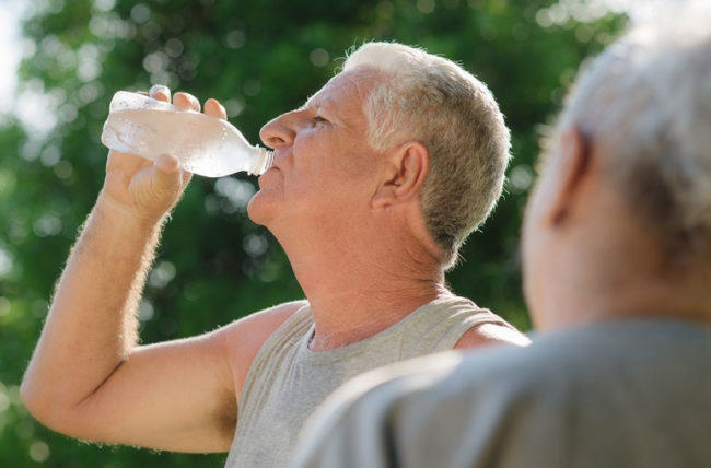 Older man drinking water after working out