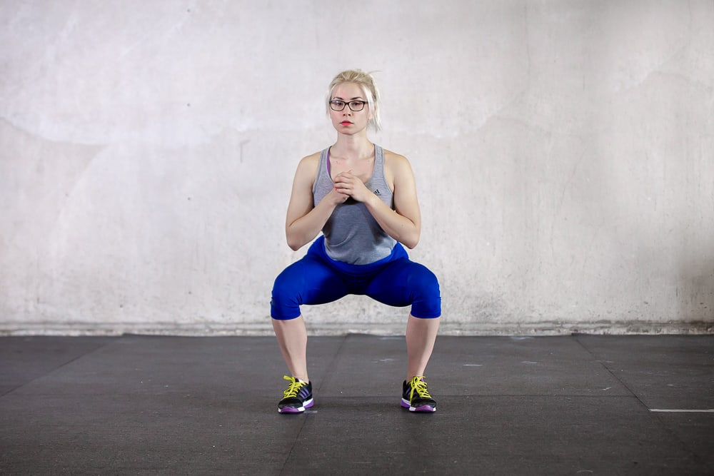 woman squatting with knees out