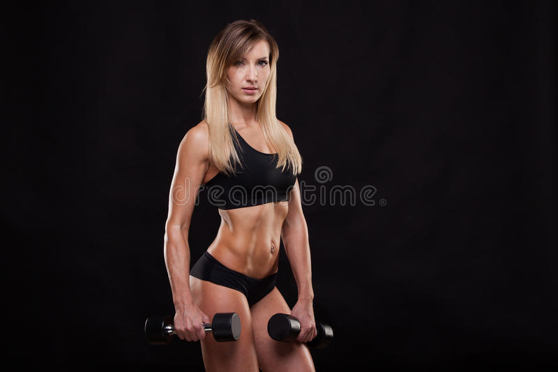 Beautiful fitness woman is lifting dumbbells. Sporty girl showing her well trained body. isolated on dark background stock images