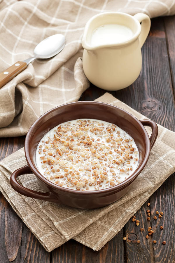 Buckwheat with milk. On a wooden table royalty free stock image