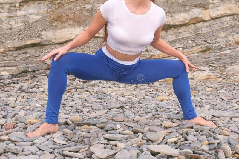 Girl is doing plie squats the bodyflex during breathing exercises on the rock background. Close-up belly and body. Unrecognizable royalty free stock image