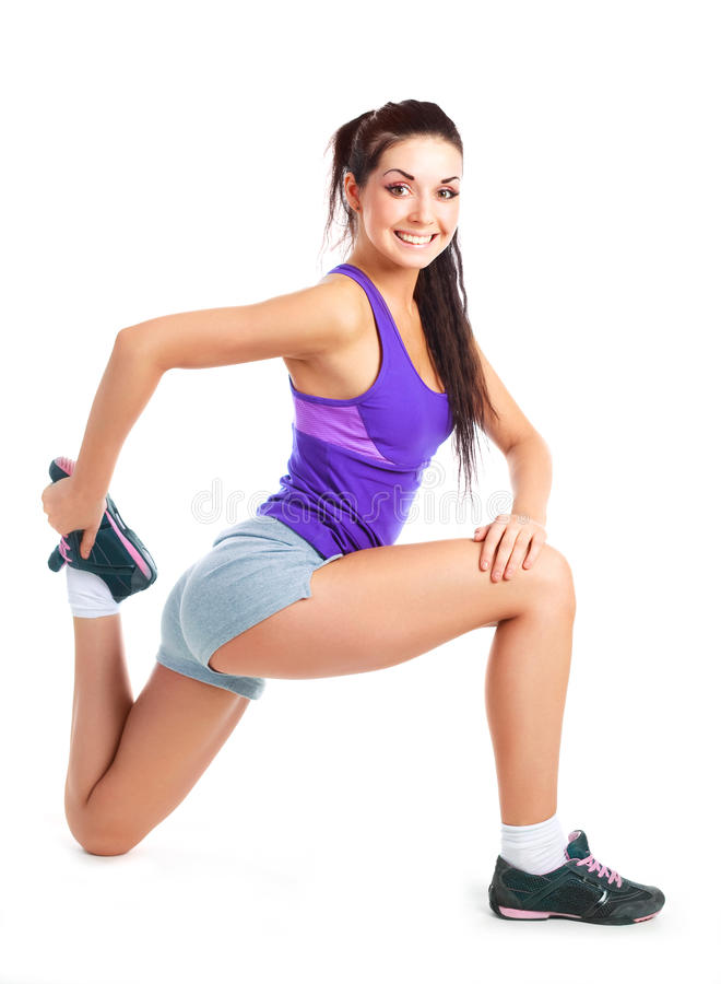 Girl stretching. Beautiful young brunette woman stretching the muscles of her legs stock image