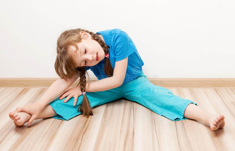 Girl stretching the muscles. Beautiful five year old girl stretching the muscles of her back and legs at home stock photos
