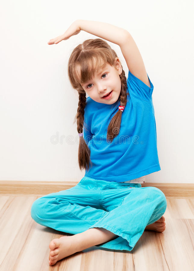 Girl stretching the muscles. Beautiful five year old girl stretching the muscles of her back and arms at home stock image