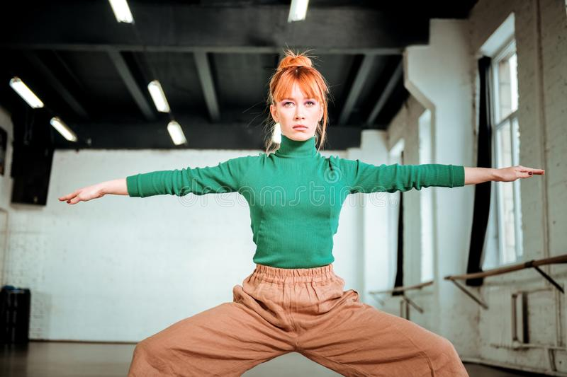 Good-looking slim yoga coach in a green turtleneck doing exercises for strong legs. Exercises for legs. Good-looking slim yoga coach wearing a green turtleneck royalty free stock photo