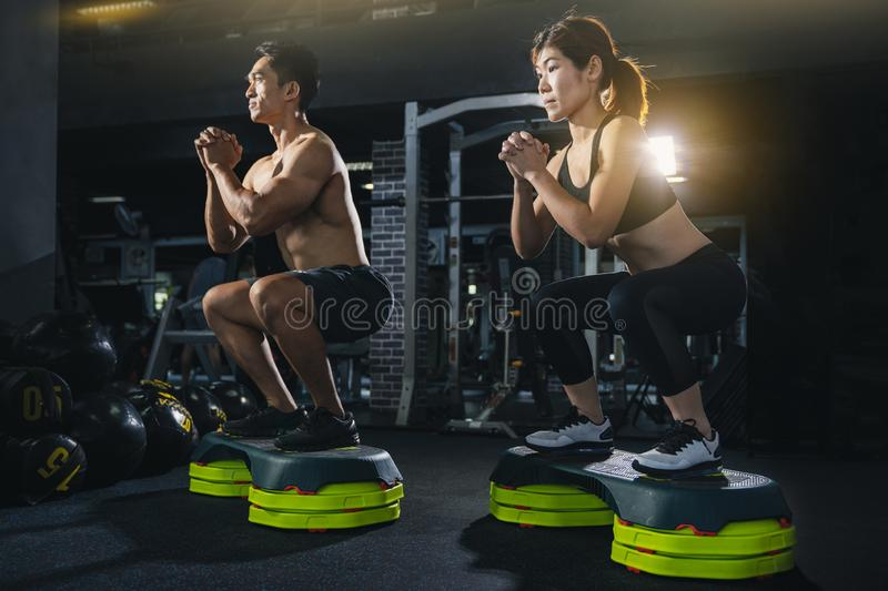 Group of healthy fitness people in gym, Young couple is working out at gym, Attractive woman and handsome muscular man are trainin royalty free stock image