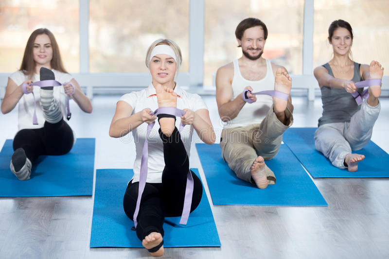 Hamstring stretch exercise. Fitness, stretching practice, group of four beautiful happy fit young people working out in sports club, doing hamstring stretch royalty free stock image
