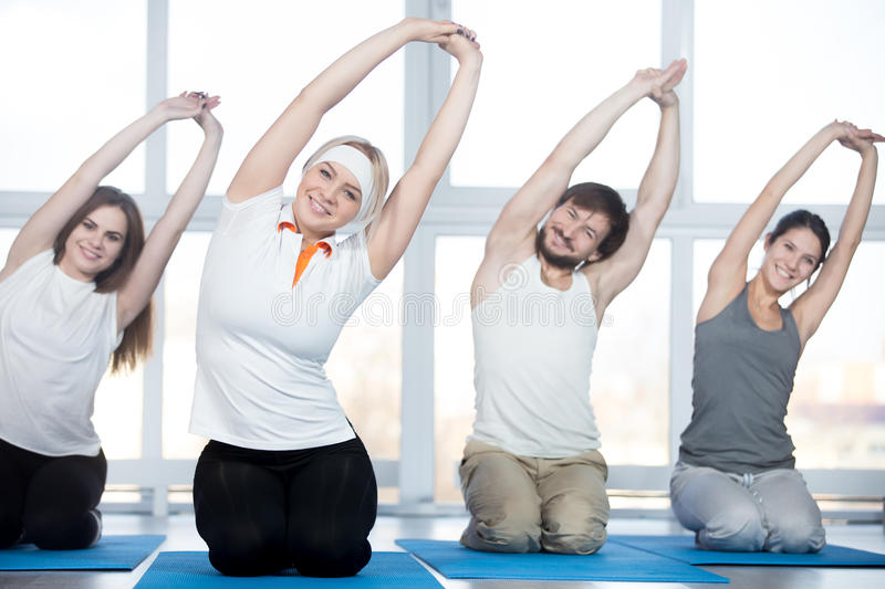 Side bend exercise. Fitness, stretching practice, group of four beautiful happy fit young people working out in sports club, doing side bend exercises with royalty free stock photos