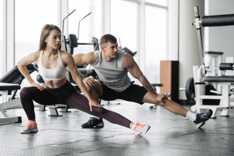 Sport, fitness, lifestyle and people concept - smiling man and woman stretching in gym royalty free stock photos