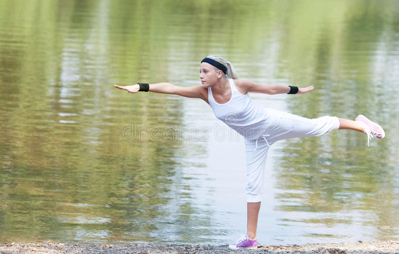 Sporty woman. Beautiful young blond woman doing yoga exercises near the lake on a warm summer day royalty free stock image