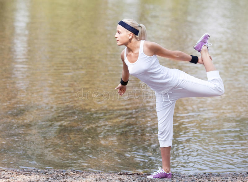 Sporty woman. Beautiful young blond woman doing yoga exercises near the lake on a warm summer day royalty free stock photo