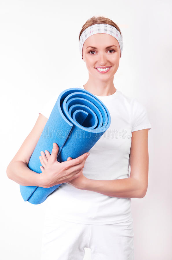 Woman with a rug. Beautiful young blond woman with a mat, going to work out stock images