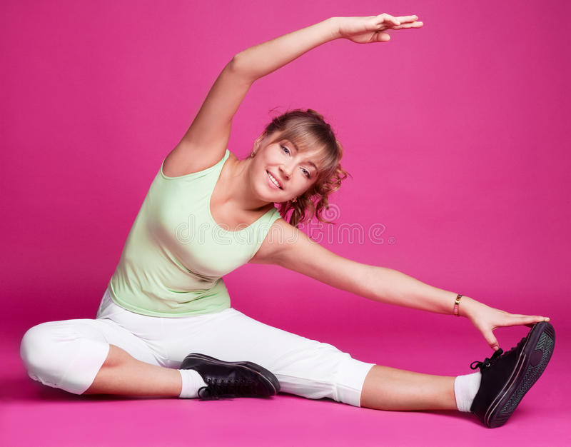 Woman stretching. Beautiful young woman stretching the muscles of her legs and back, against pink studio background stock photos