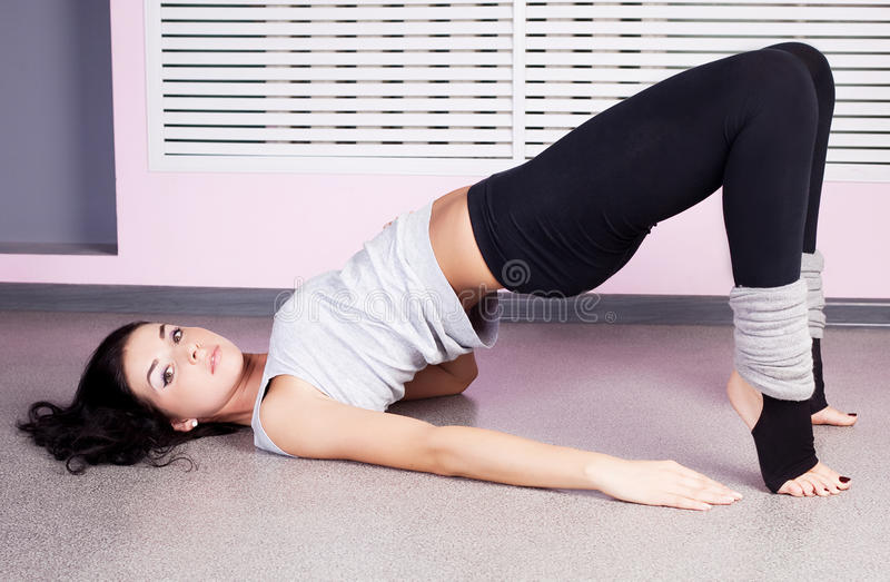 Woman stretching. Beautiful young woman stretching the muscles of legs in the gym stock images