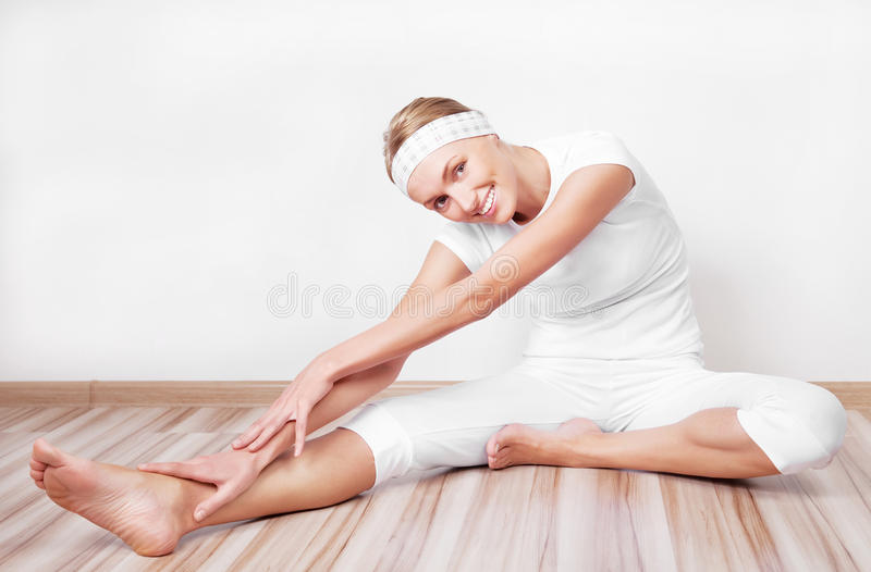 Woman stretching the muscles. Beautiful young blond woman stretching the muscles of her back and legs at home royalty free stock photo