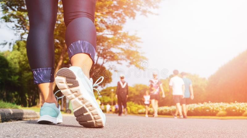 Young fitness woman legs walking with group of people exercise walking in the city public park in morning royalty free stock images