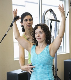 Pilates teacher using verbal and tactile feedback to ensure proper form