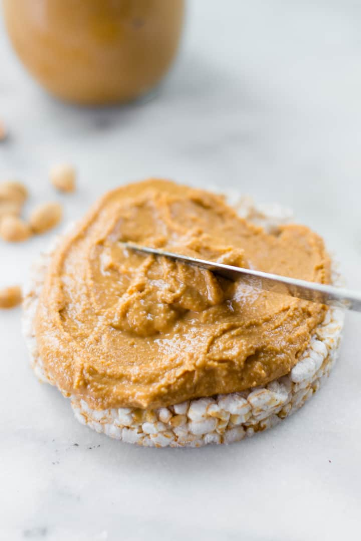 View of a knife spreading Honey Roasted Peanut Butter on a plain rice cake.