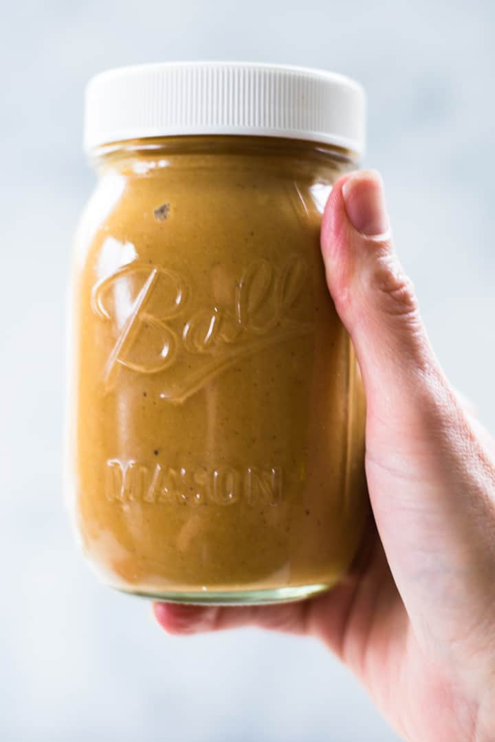 Side view of a hand holding a covered mason jar filled with Honey Roasted Peanut Butter.