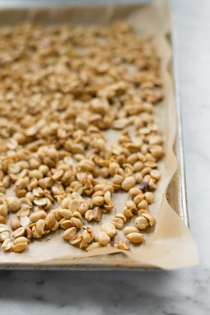 Overhead image of raw honey and salt covered roasted peanuts, ready to be put in the oven as preparation for Honey Roasted Peanut Butter.
