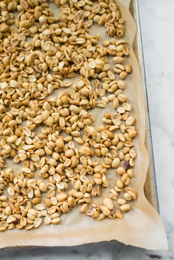 Overhead image of raw honey and salt covered roasted peanuts, coming out of the oven as preparation for Honey Roasted Peanut Butter.